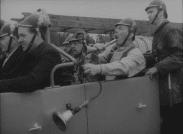 Åsa-Nisse i baksätet på en brandbil tutandes febrilt i en lur.
