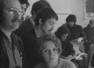 Diverse människor, en yngre kvinna i mitten tittar in i kameran.