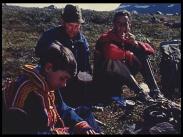 Två vuxna sportfiskare äter ute i det fria tillsammans med en tonårspojke klädd i samisk kolt.
