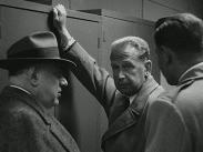 Dag Hammarskjöld lutad mot ett skåp flankerad av två män.