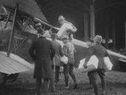 Stillbild från filmen Veckorevy 1920-03-01 so visar att flera män som lastar ett flygplan med flera paket.