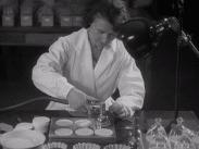 En kvinna i vit rock som arbetar i ett laboratorium.