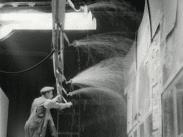 Stillbild ur journalfilmen Veckorevy 1944-03-06 som visar från inspelningen av filmen Hets där en man på stege fixar med konstgjort regn son rinner utför fönsterrutor.