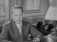 Dag Hammarskjöld tittar in i kameran sittandes vid skrivbord.
